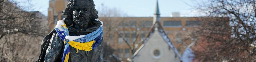 Father Marquette statue at St. Joan of Arc Chapel in winter