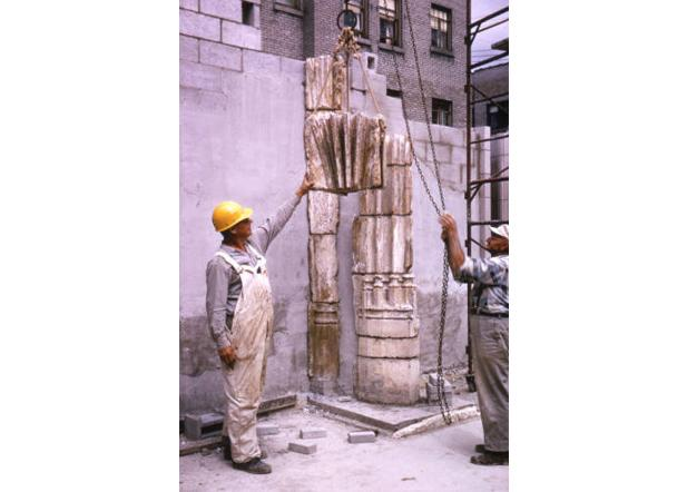 Two workers lift a stone in place as part of the Saint Joan of Arc Chapel reconstruction, 1966