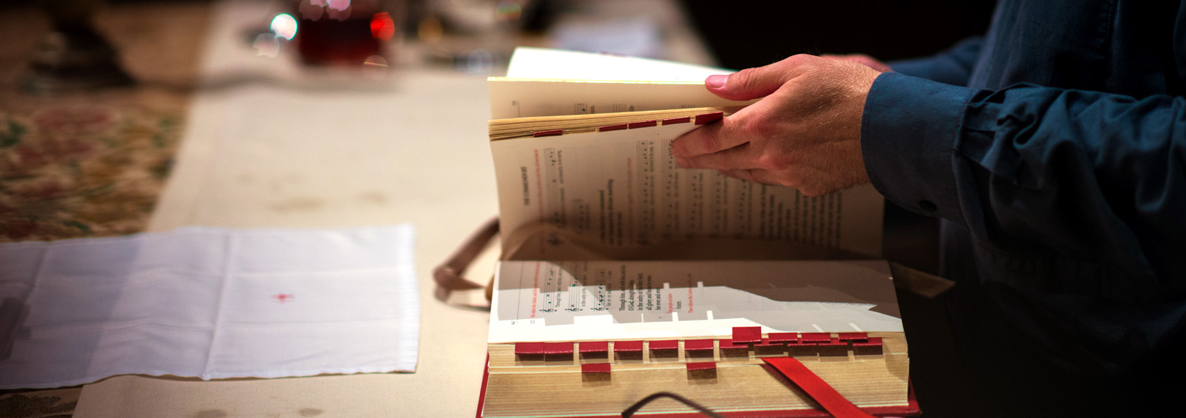 Close up of the pages of a hymn book being flipped by a priest's hands.