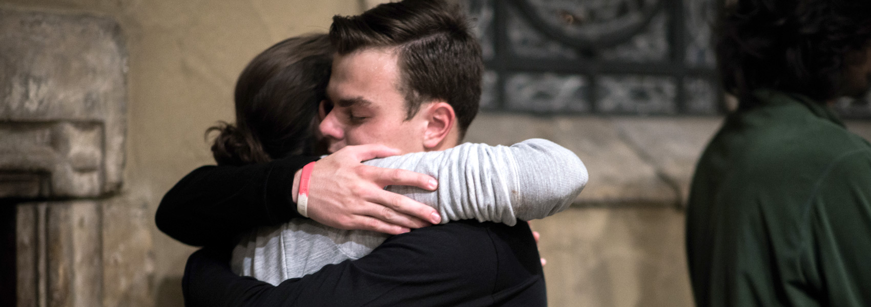 Two students hugging during a faith service inside of St. Joan of Arc chapel.