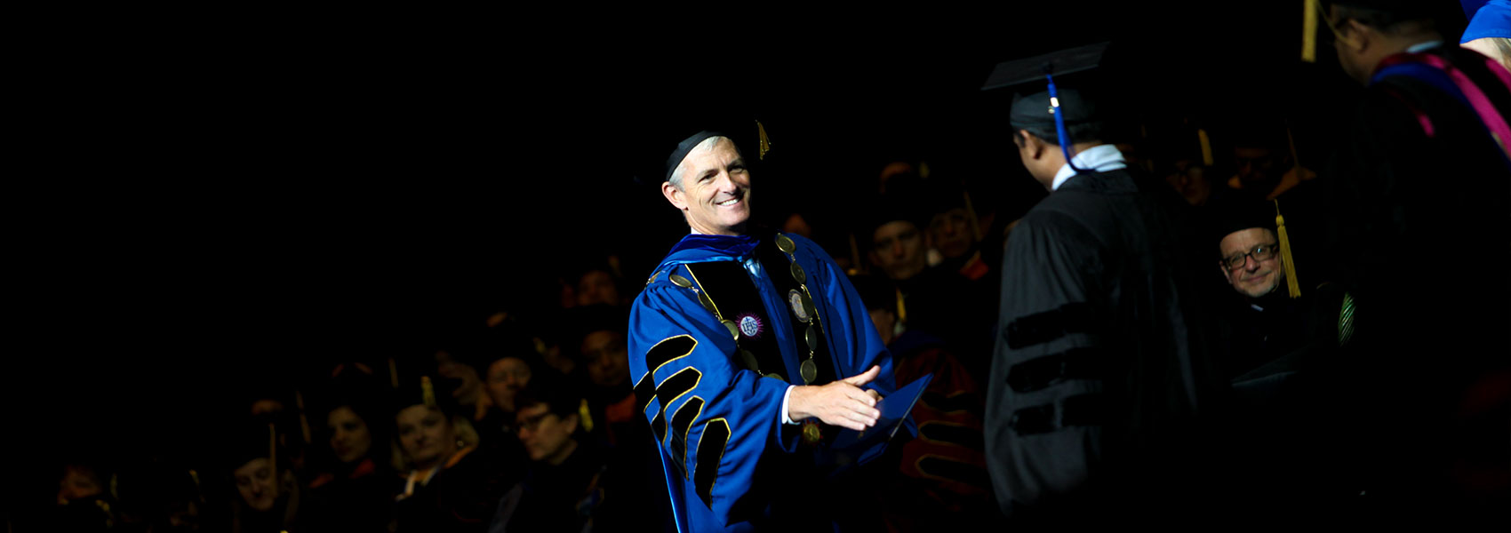 President Lovell shaking hands with a new graduate during commencement.