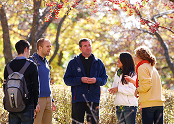 A Jesuit priest chats with students on campus
