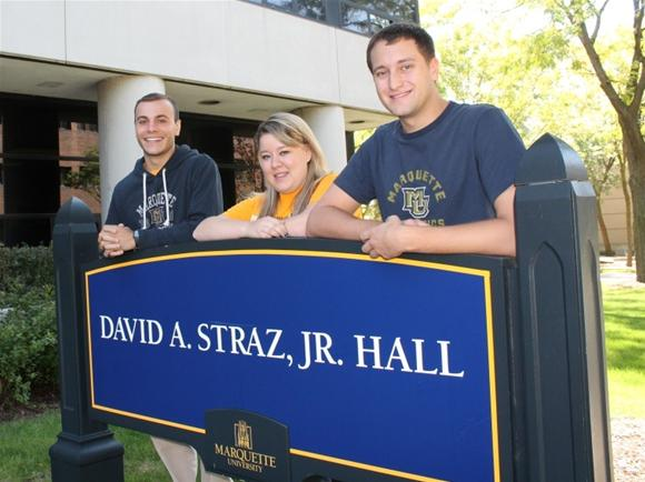 Students pose at Straz Hall sign