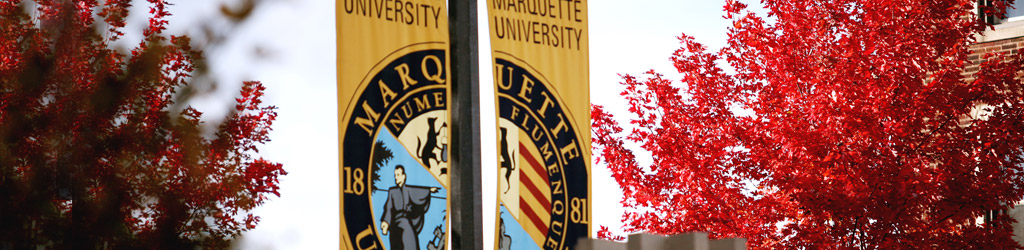 Marquette University banner on lamp post with autumn trees