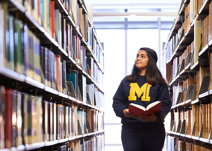 Student in library stacks