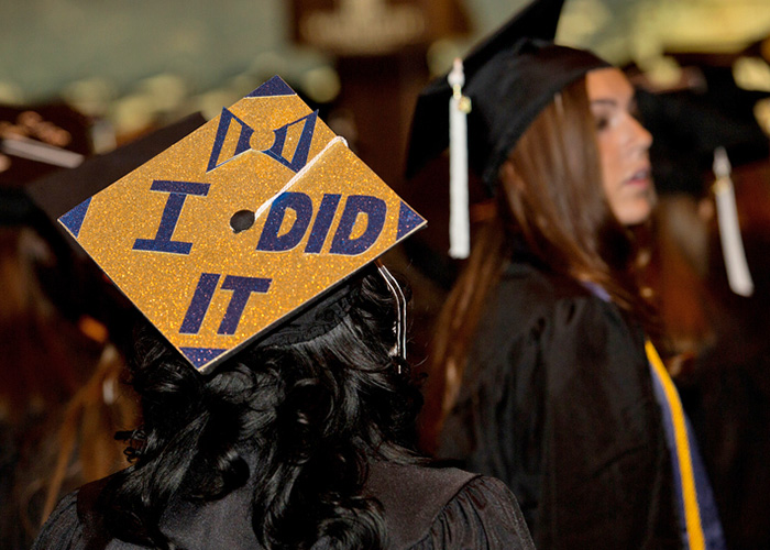 "Graduate wearing a mortarboard that reads ""I DID IT"""