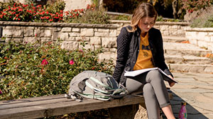 A student outside, sitting on a bench studying.