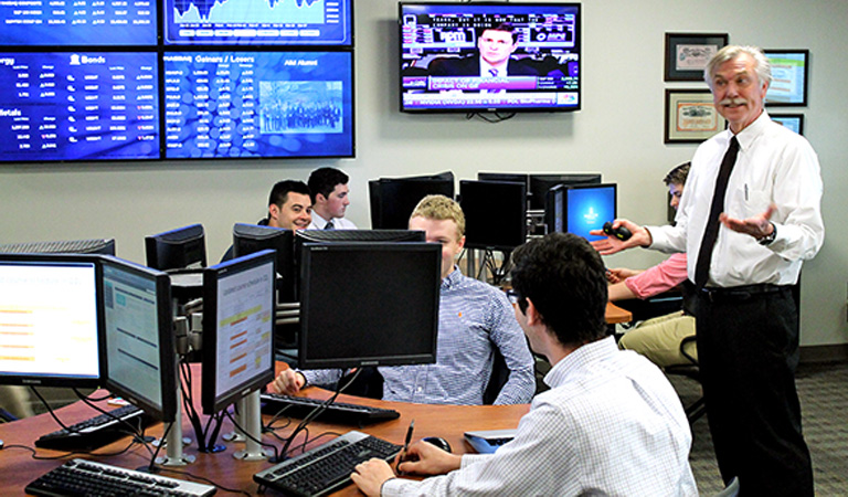 A group of investors sitting at computers with stock information on their screens. There are also tv screens hanging on the wall with stock tickers.