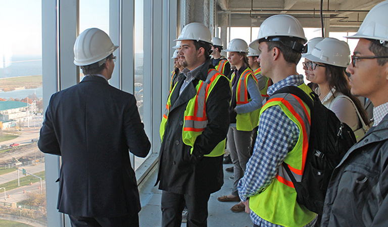 A group of people wearing construction hats and jackets, standing in a tall unfinished building, looking out of a window.
