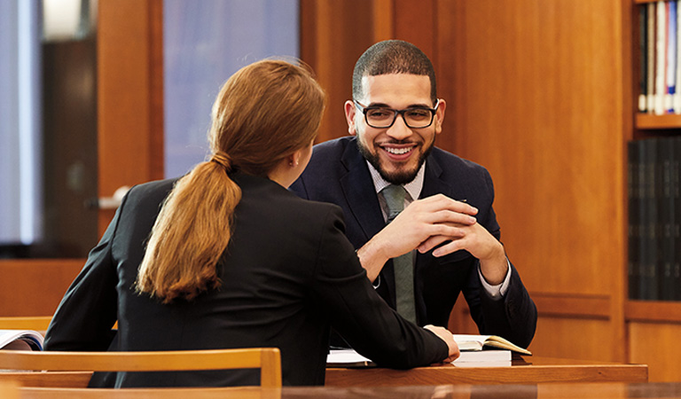 A man and woman in business attire having a conversation sitting at a table.