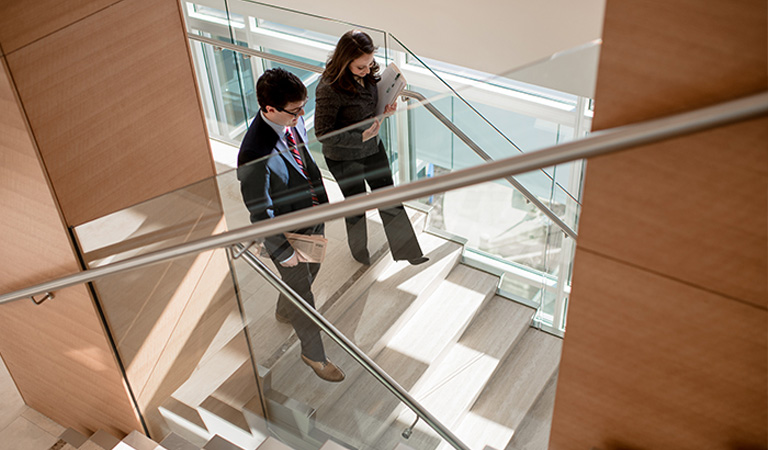 A man and woman walking down steps in an office building.