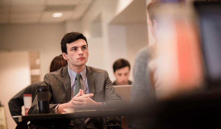 A focused picture of a young man in business attire sitting at a table with his hands folded in a room full of other people.