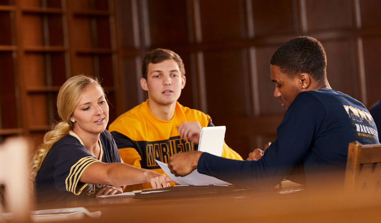 Three students sitting at a table sharing information.
