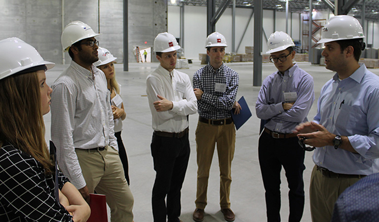 A group of men and women, dressed business casual, wearing construction hats in a mostly empty warehouse.