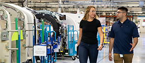 A woman and man walking by machines in an engineering facility.