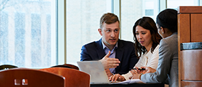Three business graduate students talking at a table in front of a computer