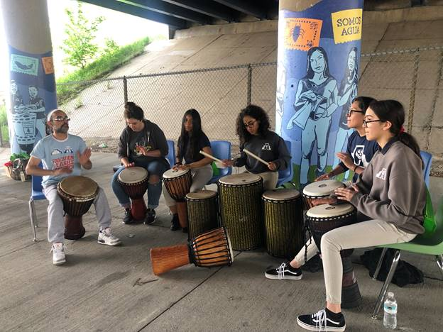 Celebrating the completed mural with Latino Arts Inc. drumming instructor Cecilio Negron and some of the students