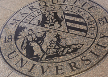Marquette University seal set in the floor of Raynor Library's lobby