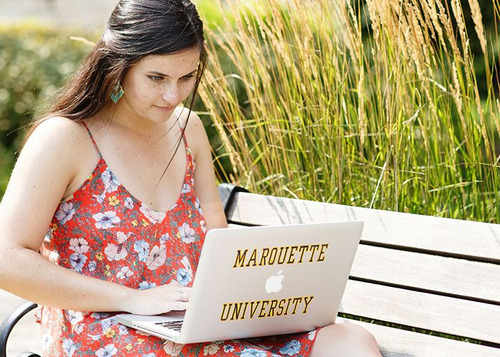 Student outdoors using laptop with Marquette University decal
