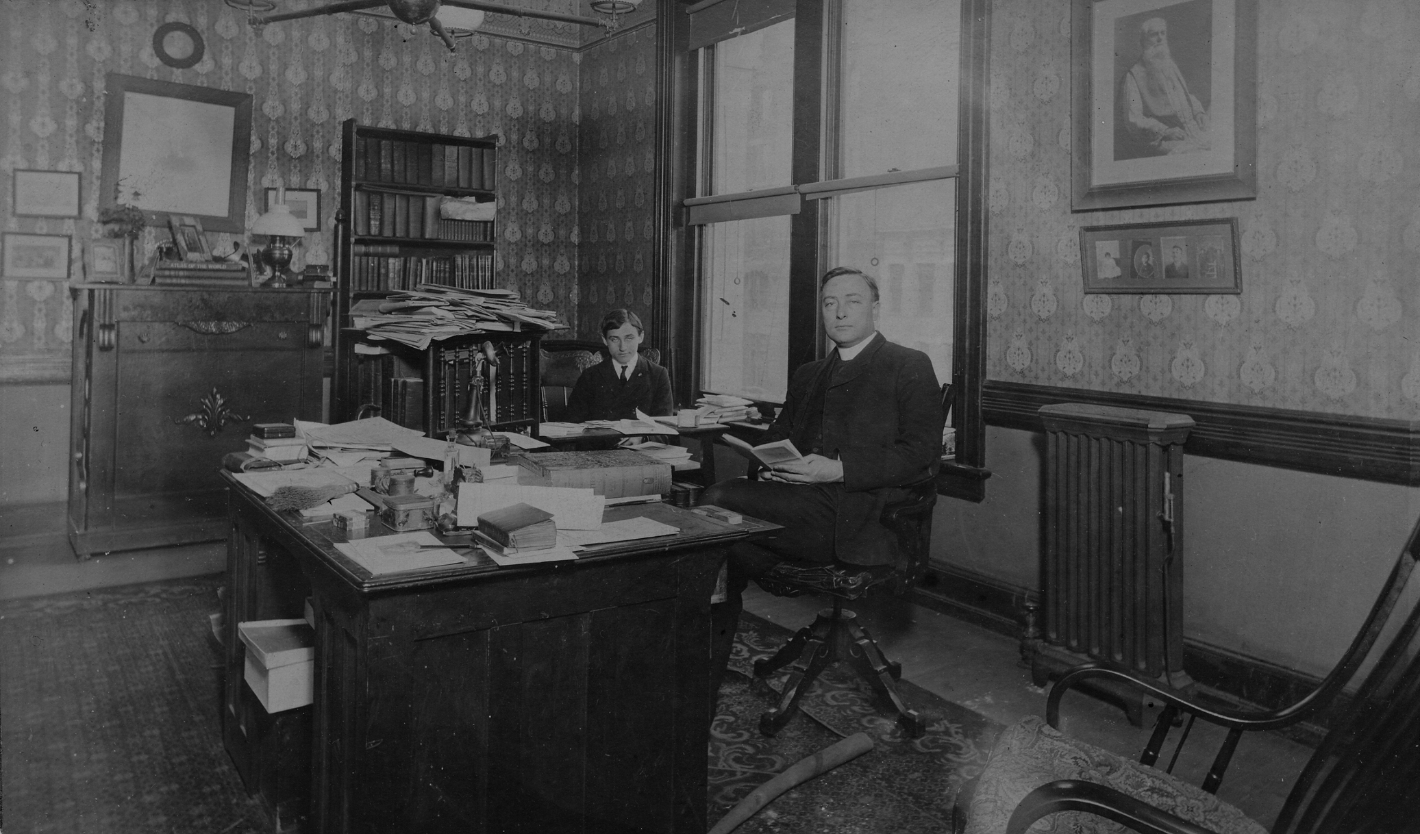 Monsignor William Henry Ketcham with his adopted son Tom (Choctaw), in his office at the Bureau of Catholic Indian Missions