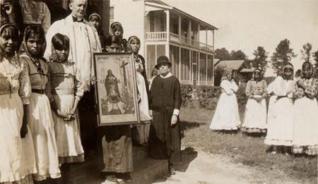 Choctaw Indian children holding a poster of St. Kateri Tekakwitha and joined by a priest of the Missionary Servants of the Most Holy Trinity and a sister of the Missionary Servants of the Blessed Trinity at Holy Rosary Mission, Tucker, Mississippi, 1934