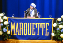 Mother Teresa seated at table with Marquette banner