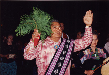 Deacon with pine boughs in his hands in Tekakwitha Conference procession, 