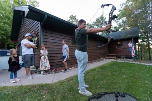 A man shooting a bow and arrow in small-town Wisconsin