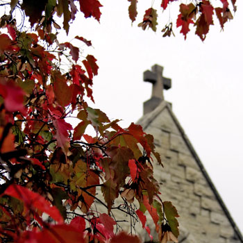 The cross on top of St. Joan of Arc Chapel framed by fall leaves