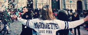 Student facing a crowd, wearing a Marquette sweatshirt