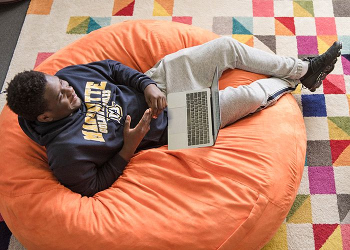 Student on beanbag with MacBook